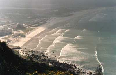 view over Muizenberg with sun on breaking waves